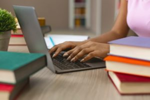 Hands of black female student typing on laptop keyboard
